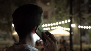 Man standing back and talking on cellphone at night in public place