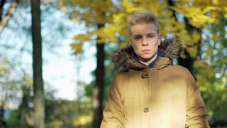 Man standing in the autumnal park and looking to the camera