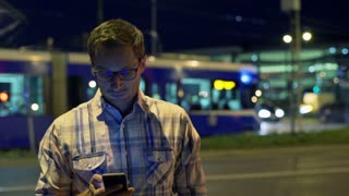 Man standing in the city at night and talking on cellphone, steadycam shot
