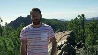 Man standing in the mountains and doing serious look to the camera