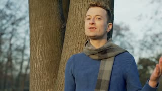 Man standing in the park and telling something to the camera, steadycam shot