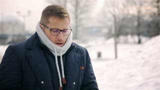 Man standing in the park at winter time and blowing nose