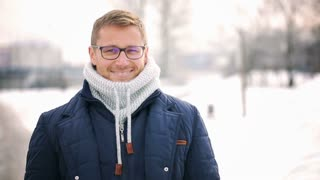Man standing in the park at winter time and smiling to the camera