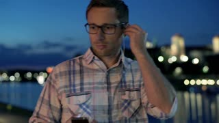 Man standing next to the river and start listening music at night, steadycam sho