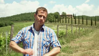 Man standing next to the vineyard and smiling to the camera, steadycam shot