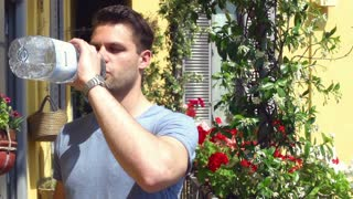 Man standing on the balcony and drinking water from the bottle, steadycam