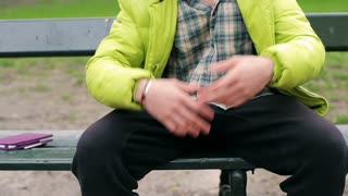 Man talking and gesturing while sitting on the bench