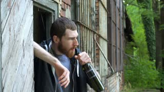Man tasting wine while drinking it next to the abandoned building