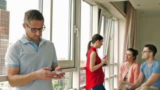 Man texting on smartphone and friends talking in the background