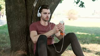 Man texting on smartphone and listening music while sitting in the park