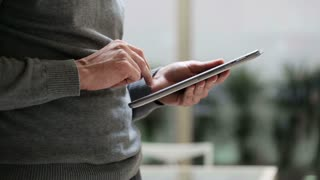 Man touching screen and browsing on tablet, closeup.