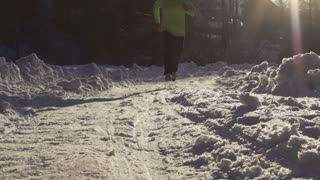 Man training on the snowy road, steadycam shot, slow motion shot at 240fps