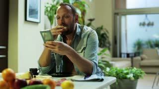 man using his cellphone and eating sandwich