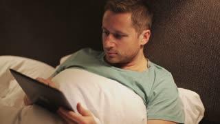Man using tablet in bedroom