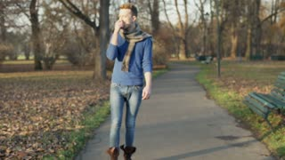 Man walking in the autumnal park and eating an apple, steadycam shot
