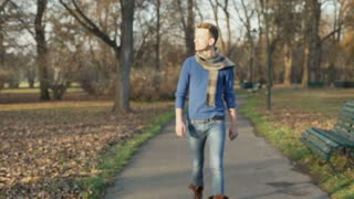 Man walking in the autumnal park and smiling to the camera, steadycam shot