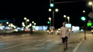 Man walking in the city at night and smiling to the camera, steadycam shot