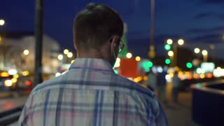 Man walking in the city at night next to the road traffic, steadycam shot