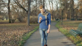 Man walking on the pathway in the park and texting on smartphone, steadycam shot