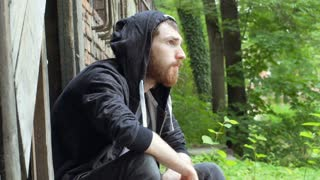 Man wearing hood and looking thoughtful while sitting next to the cinders