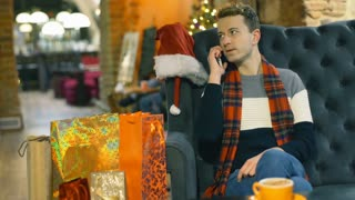 Man wearing tartan scarf and speaking on cellphone in the festive cafe, steadycam shot