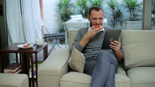 man with tablet eating a sandwich and sitting on the sofa