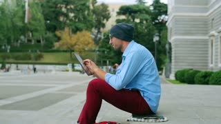 Man working on tablet and sitting on public square