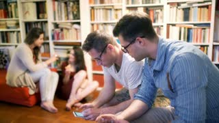 Men sitting at home and browsing internet on smartphone