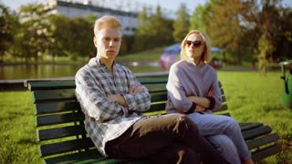Morose couple sitting on the bench in the park