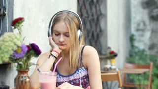 Morose girl looking thoughtful while listening music in the outdoor cafe