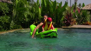 Mother and son falling out from toy to the pool, slow motion shot