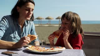Mother eating pizza with her son in the restaurant on the beach, steadycam shot