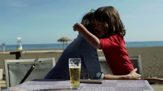 Mother hugging his son while sitting in the restaurant on the beach, steadycam s