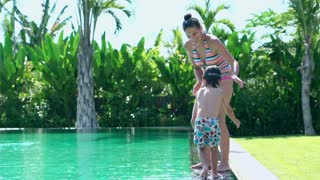 Mother jumping with her son into swimming pool and having fun
