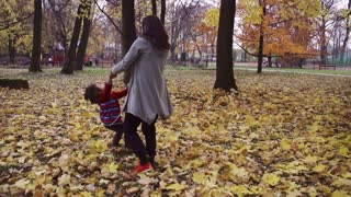 Mother spinning round with her son, steadycam shot, slow motion shot at 240fps