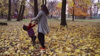 Mother spinning round with her son, steadycam shot, slow motion shot