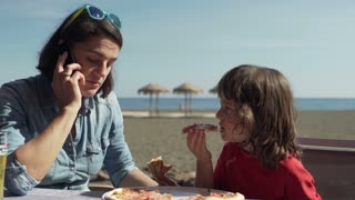 Mother talking on cellphone and eating pizza with her son, steadycam shot