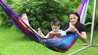 Mum and son using tablet and cellphone in a hammock, slow motion shot at 240fps