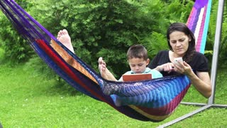 Mum and son using tablet and cellphone in a hammock, slow motion shot at 60fps