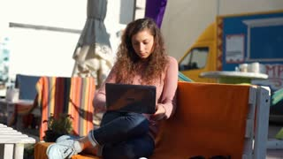 Occupied girl sitting outdoors and browsing internet on laptop