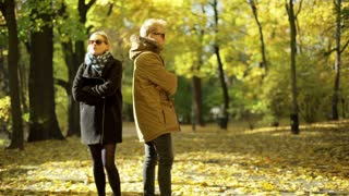 Offended couple standing in the park and not talking with each other