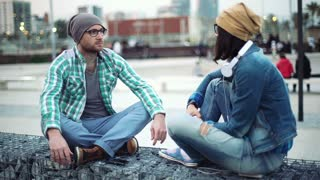 Pair of hipsters sitting in the city and chatting with each other