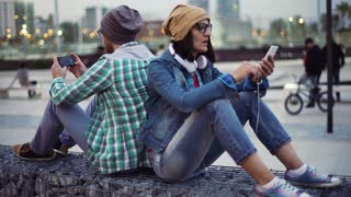 Pair of hipsters sitting in the city at the evening and relaxing