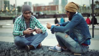 Pair of hipsters using smartphone at night in the city