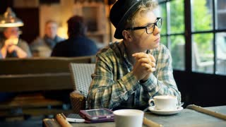 Pensive boy sitting in the cafe and eating mousse from coffee