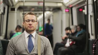 Pensive businessman riding by the subway, steadycam shot