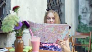 Pensive girl sitting in the outdoor cafe and reading map