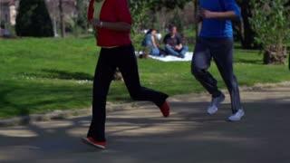 People jogging in park, slow motion shot at 120fps, steadycam shot