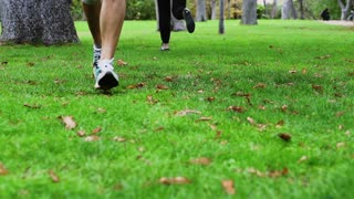 People jogging in the park in trainers, slow motion shot at 240fps, steadycam