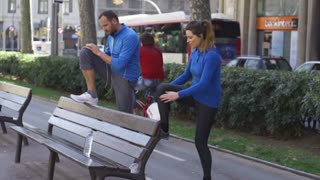 People stretching on street bench, slow motion shot at 60fps, steadycam shot
